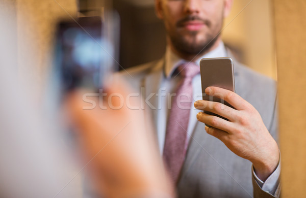 close up of man in suit taking mirror selfie Stock photo © dolgachov
