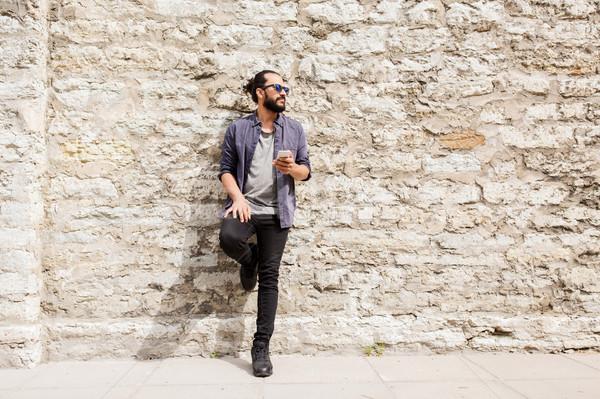 Uomo smartphone muro di pietra strada urbana tempo libero tecnologia Foto d'archivio © dolgachov