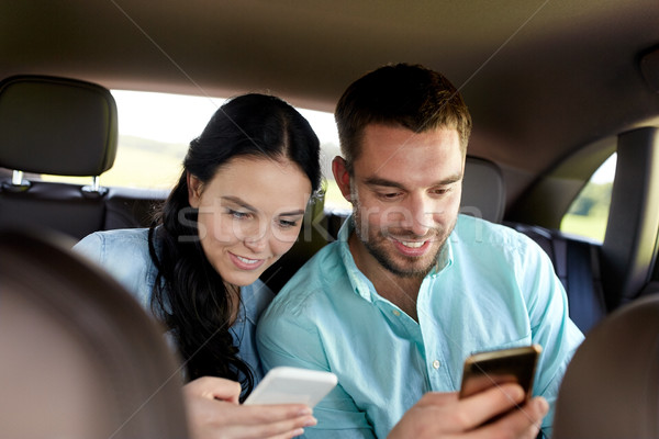 man and woman with smartphones driving in car Stock photo © dolgachov