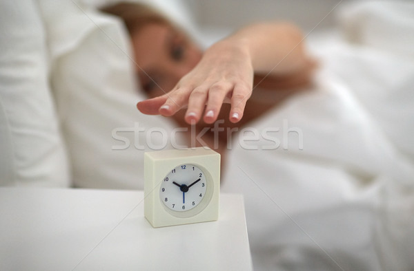 close up of woman with alarm clock in bed at home Stock photo © dolgachov