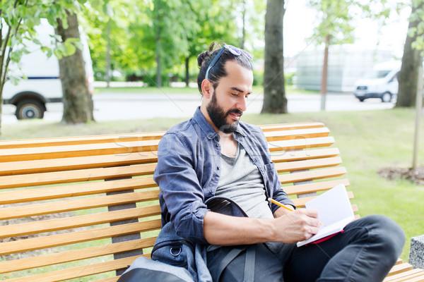 man writing to notebook or diary on city street Stock photo © dolgachov