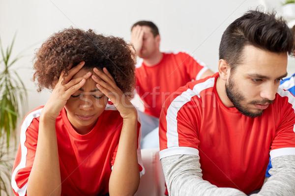 sad friends or football fans at home Stock photo © dolgachov