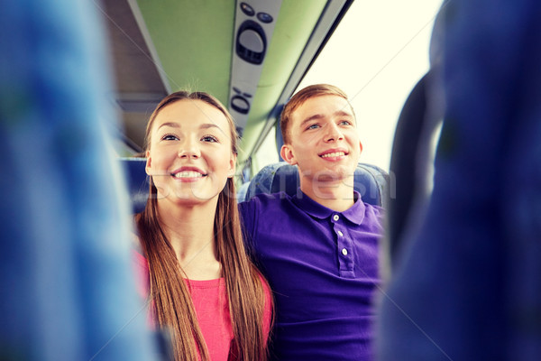 happy teenage couple or passengers in travel bus Stock photo © dolgachov