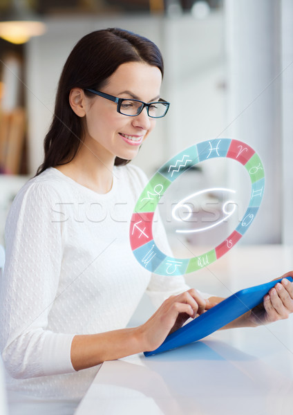 woman with tablet pc and zodiac signs at cafe Stock photo © dolgachov