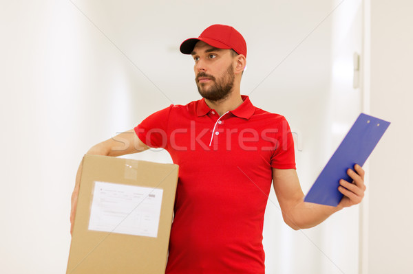 delivery man with box and clipboard in corridor Stock photo © dolgachov