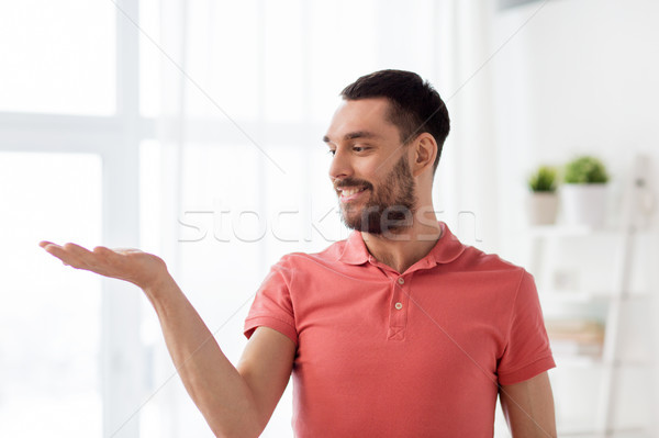 happy man holding something imaginary at home Stock photo © dolgachov