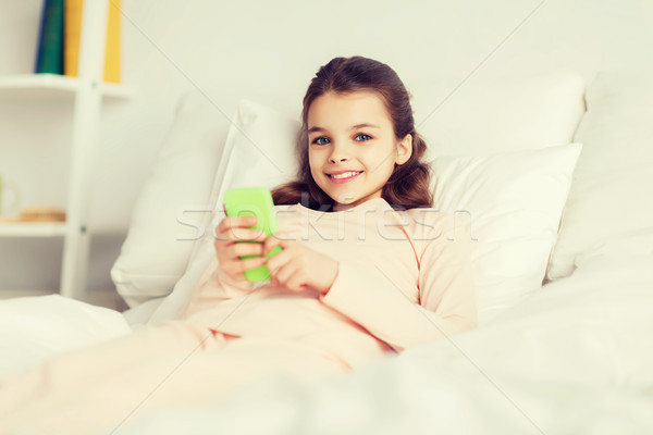 happy girl lying in bed with smartphone at home Stock photo © dolgachov