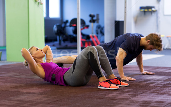 woman with man doing sit ups and push ups in gym Stock photo © dolgachov