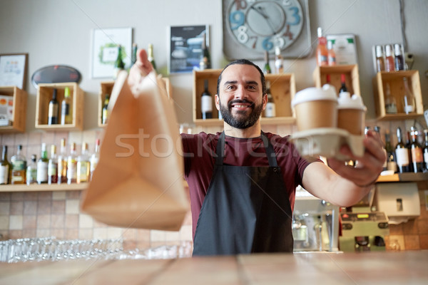 man or waiter with coffee and paper bag at bar Stock photo © dolgachov