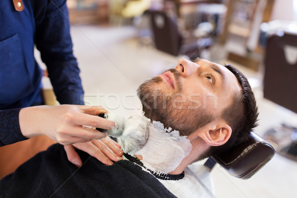 man and barber applying shaving foam to beard Stock photo © dolgachov