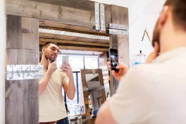 man taking selfie by smartphone at barbershop Stock photo © dolgachov