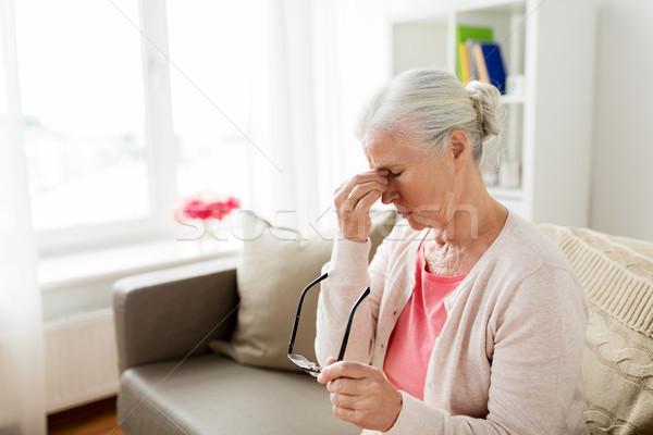 senior woman with glasses having headache at home Stock photo © dolgachov