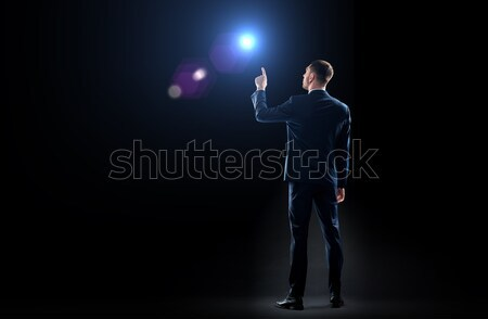 businessman in suit pointing finger to lens flare Stock photo © dolgachov