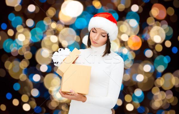 displeased woman in santa hat with christmas gift Stock photo © dolgachov