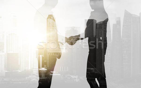 Iş adamları el sıkışmak şehir iş işbirliği Stok fotoğraf © dolgachov