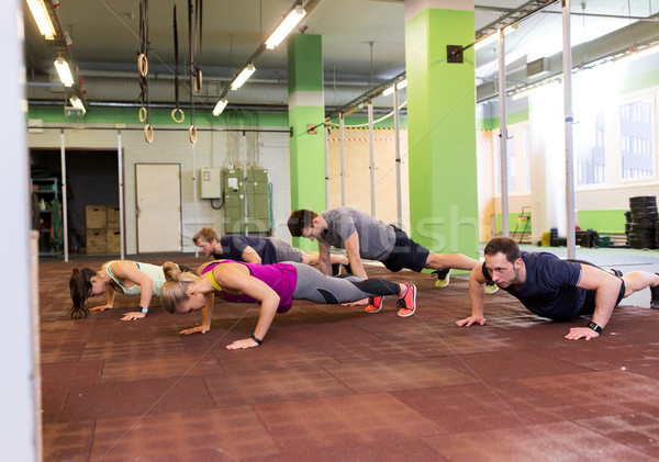 group of people doing push-ups in gym Stock photo © dolgachov