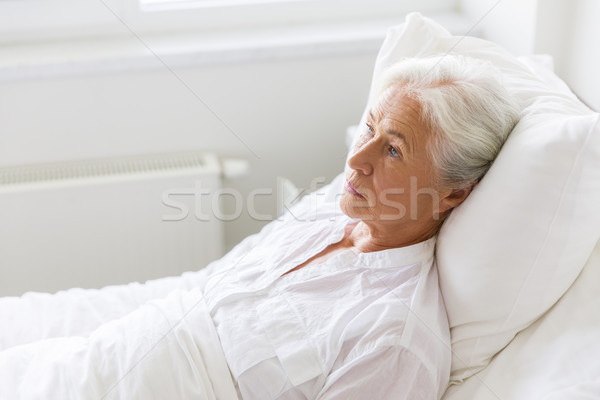 sad senior woman lying on bed at hospital ward Stock photo © dolgachov