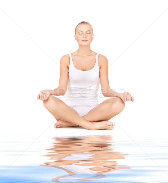 woman practicing yoga lotus pose on white sand Stock photo © dolgachov