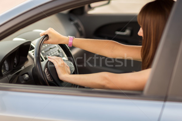 woman driving a car with hand on horn button Stock photo © dolgachov