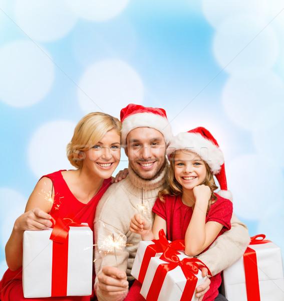 smiling family holding gift boxes and sparkles Stock photo © dolgachov