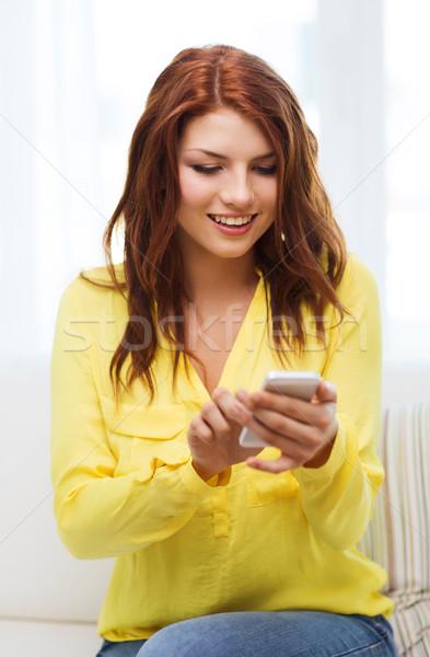 Mosolygó nő okostelefon otthon technológia internet ül Stock fotó © dolgachov