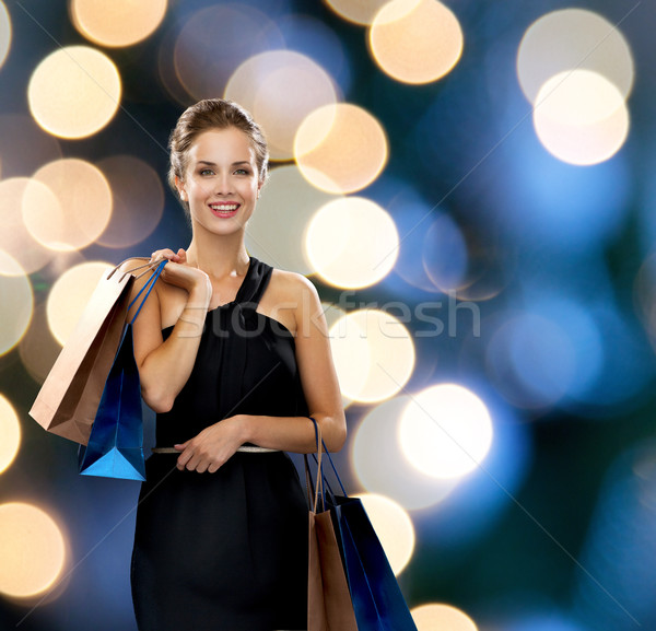 smiling woman in dress with shopping bags Stock photo © dolgachov