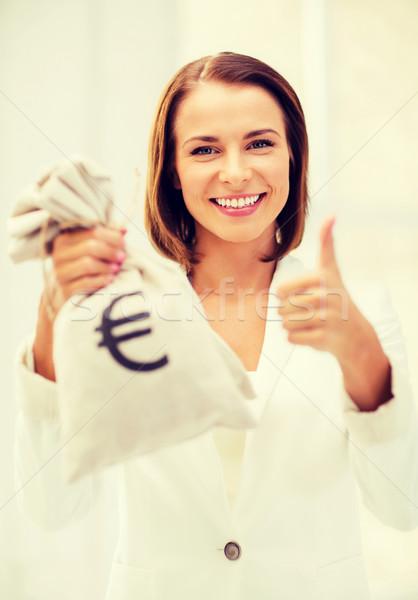 businesswoman holding money bag Stock photo © dolgachov