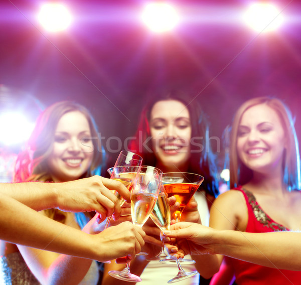 three smiling women with cocktails and disco ball Stock photo © dolgachov