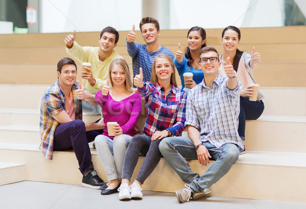 group of smiling students with paper coffee cups Stock photo © dolgachov