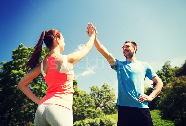 Stock photo: two smiling people making high five outdoors