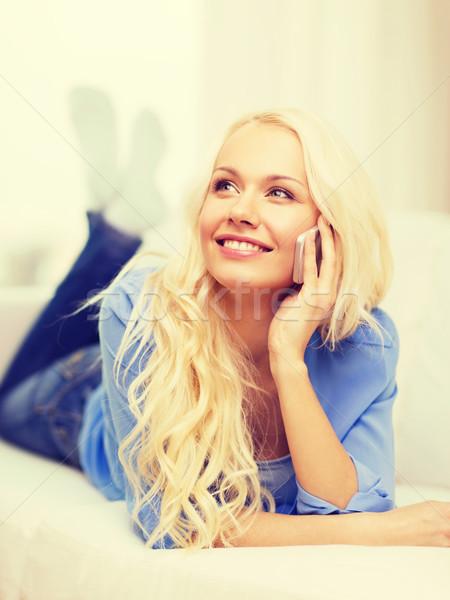 улыбающаяся женщина смартфон домой технологий связи диване Сток-фото © dolgachov