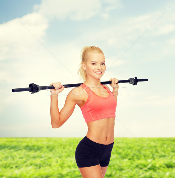 Stock photo: smiling sporty woman exercising with barbell