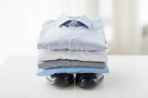 close up of folded male shirts and shoes on table Stock photo © dolgachov