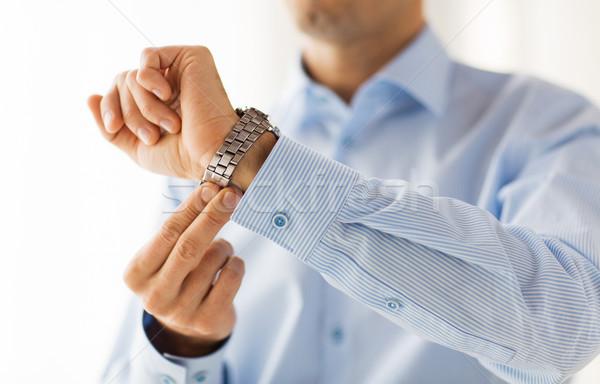 close up of man in shirt fastening wristwatch Stock photo © dolgachov