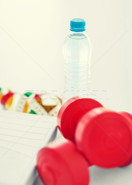 scales, dumbbells, bottle of water, measuring tape Stock photo © dolgachov