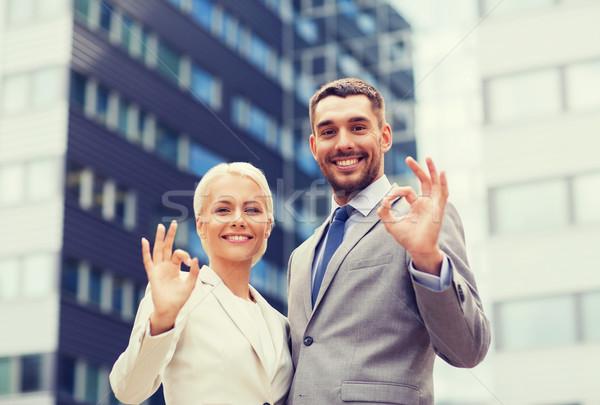 Sorridente empresários em pé prédio comercial negócio Foto stock © dolgachov