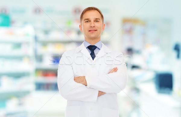 smiling male pharmacist in white coat at drugstore Stock photo © dolgachov