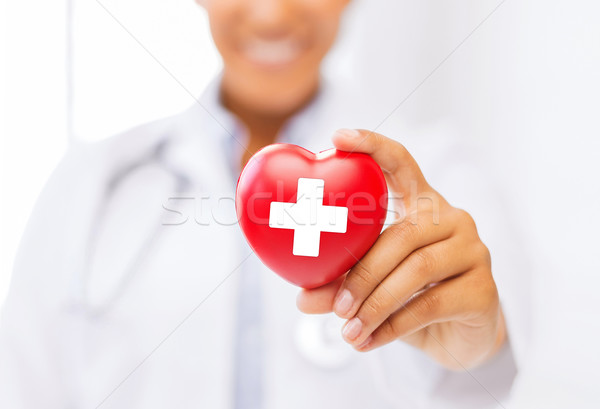 female doctor holding heart with red cross symbol Stock photo © dolgachov