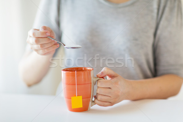 close up of woman adding sugar to tea cup Stock photo © dolgachov