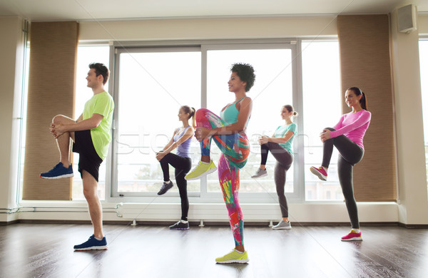 group of smiling people exercising in gym Stock photo © dolgachov