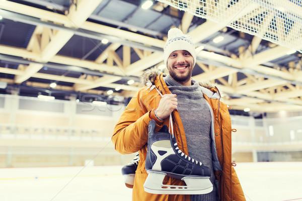 happy young man with ice-skates on skating rink Stock photo © dolgachov