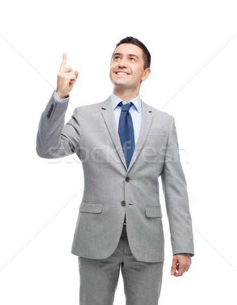 happy businessman in suit pointing finger up Stock photo © dolgachov