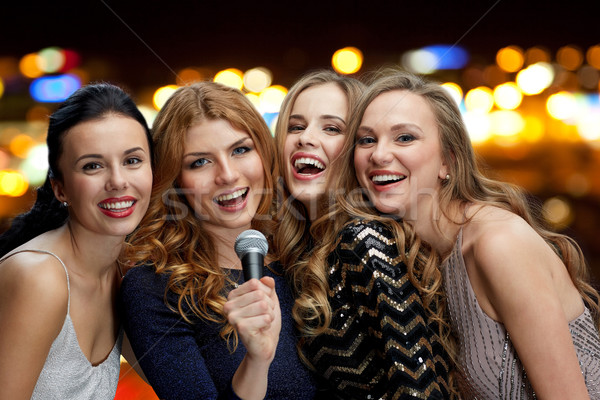 happy women with microphone singing over lights Stock photo © dolgachov