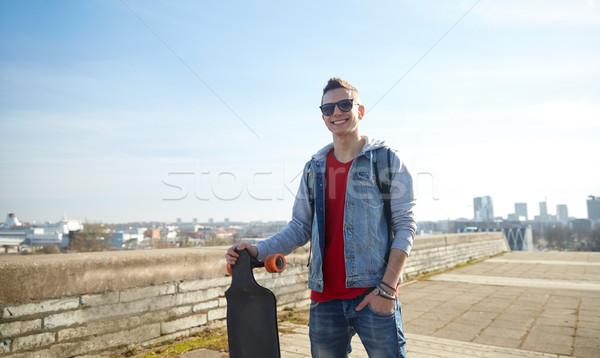 smiling teenager with longboard on street Stock photo © dolgachov