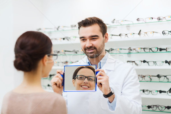 Donna occhiali guardando specchio ottica store Foto d'archivio © dolgachov