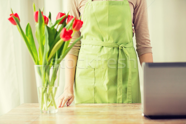 close up of woman with tulips in vase and laptop Stock photo © dolgachov