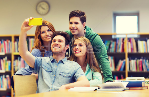 students with smartphone taking selfie in library Stock photo © dolgachov