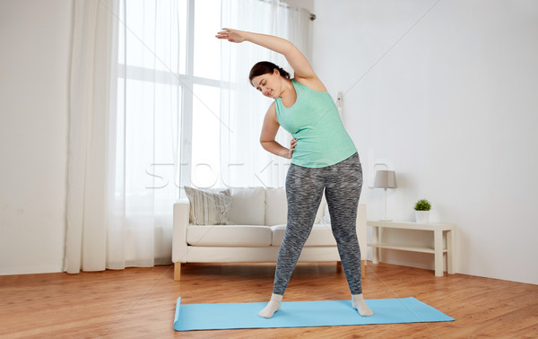plus size woman exercising on mat at home Stock photo © dolgachov