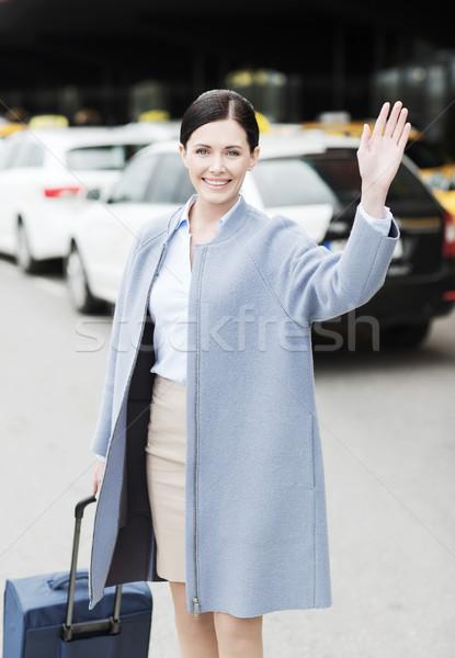 smiling young woman with travel bag waving hand Stock photo © dolgachov