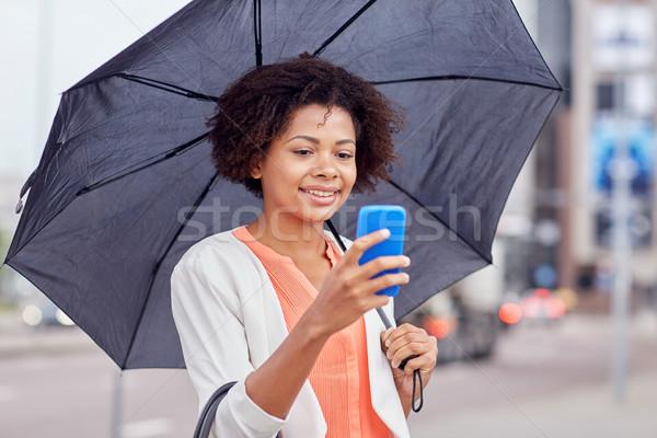 businesswoman with umbrella texting on smartphone Stock photo © dolgachov